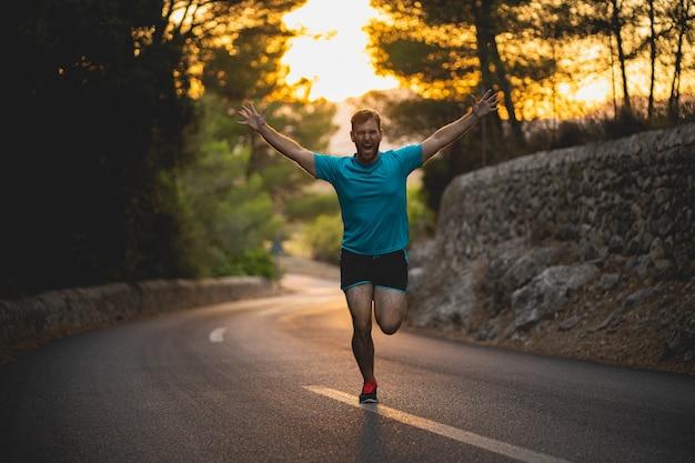 Mężczyzna w niebieskiej koszuli biegnie z podniesionymi rękami na drodze podczas zachodu słońca