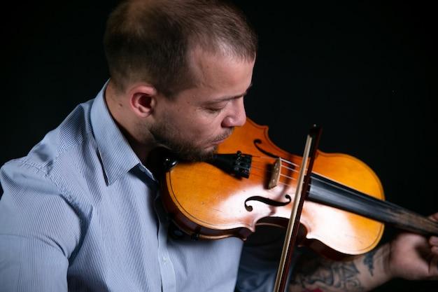 Mężczyzna w niebieskiej koszuli gra na skrzypcach.