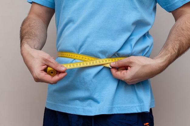 Mężczyzna w niebieskiej koszuli mierzy talię żółtą taśmą