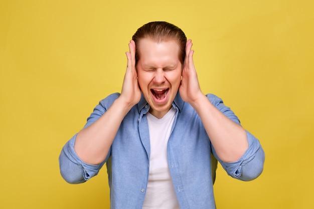 Mężczyzna w niebieskiej koszuli na żółtym tle trzyma ręce przy głowie, przedstawiając głośny krzyk różnych myśli.