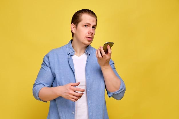 Mężczyzna w niebieskiej koszuli na żółtym tle wysyła dźwiękową wiadomość w smartfonie.