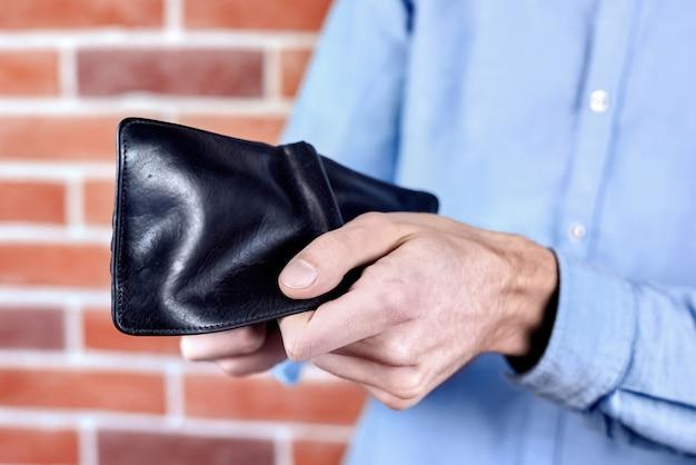 Mężczyzna w niebieskiej koszuli przedstawiający czarny pusty portfel
