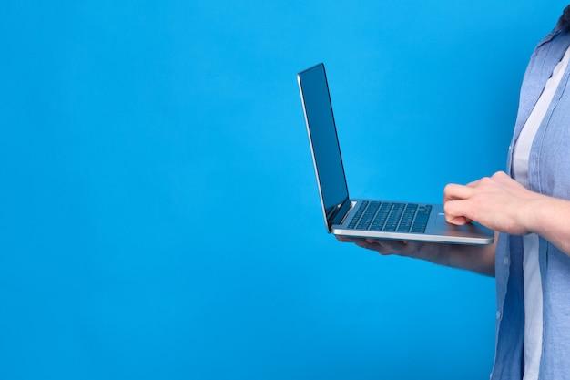 Mężczyzna w niebieskiej koszuli trzyma laptopa. koncepcja materiałów do nauki dla studentów w internecie. skopiuj miejsce