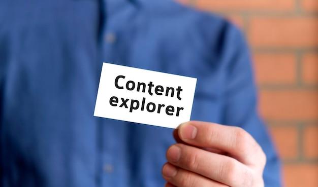 Mężczyzna w niebieskiej koszuli trzyma w jednej ręce tabliczkę z tekstem content explorer