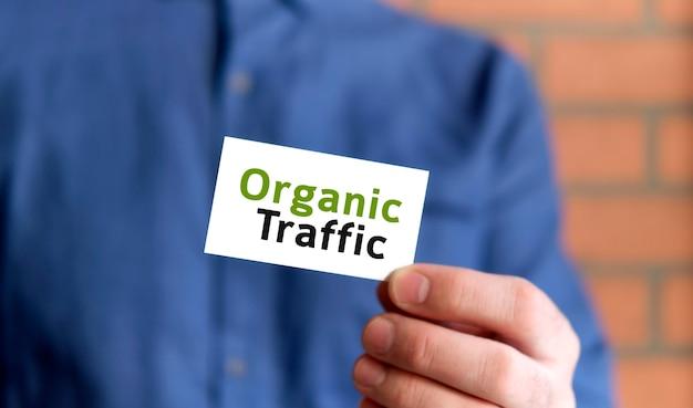 Mężczyzna w niebieskiej koszuli trzyma w jednej ręce znak z tekstem organic traffic