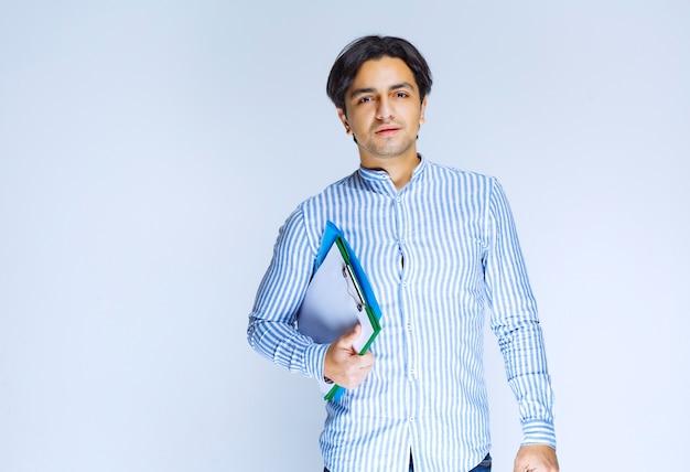 Mężczyzna w niebieskiej koszuli trzyma zielony folder sprawozdawczy. zdjęcie wysokiej jakości