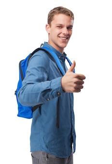 Mężczyzna w niebieskiej koszuli uśmiecha się i z plecakiem