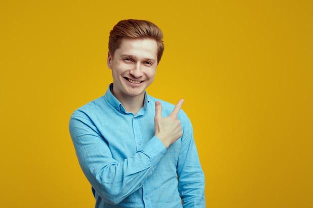 Mężczyzna w niebieskiej koszuli uśmiechający się i wskazujący na pomarańczową ścianę
