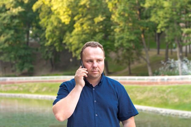 Mężczyzna w niebieskiej koszuli używa swojego smartfona
