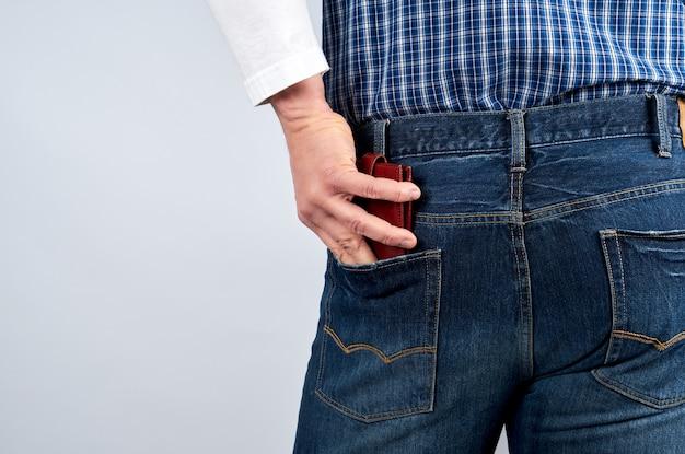 Mężczyzna w niebieskiej koszuli w kratę i dżinsach wkłada skórzany portfel do tylnej kieszeni