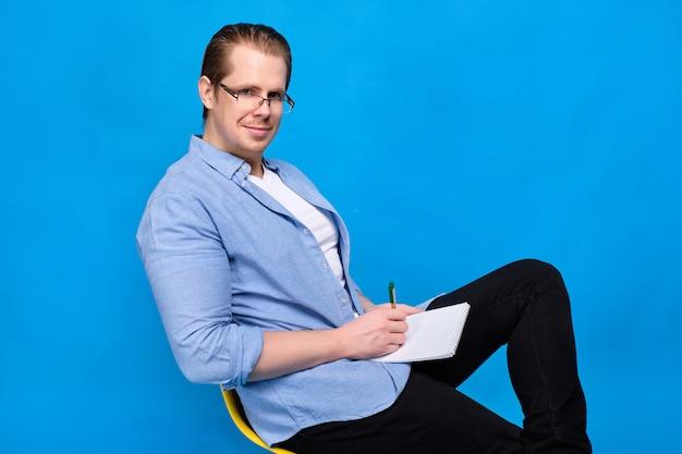 Mężczyzna w niebieskiej koszuli w okularach z notatnikiem i długopisem patrzy w kamerę. pojęcie młodego nauczyciela.