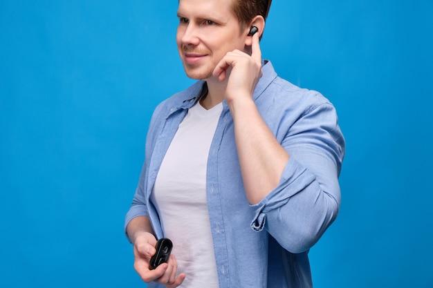 Mężczyzna w niebieskiej koszuli włożył bezprzewodową słuchawkę i włączył muzykę.