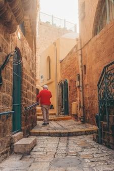Mężczyzna w niebieskiej kurtce, chodzenie po chodniku w ciągu dnia