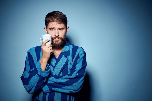 Mężczyzna w niebieskiej szacie w paski, trzymając w ręku biały kubek i zabawny model niespodzianki emocje