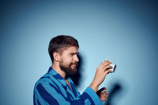 Mężczyzna w niebieskiej szacie w paski, trzymając w ręku biały kubek