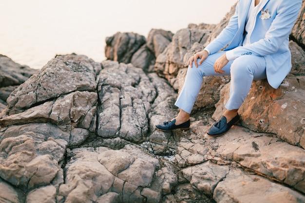 Mężczyzna w niebieskim garniturze z butonierką i mokasynami siedzi na skałach