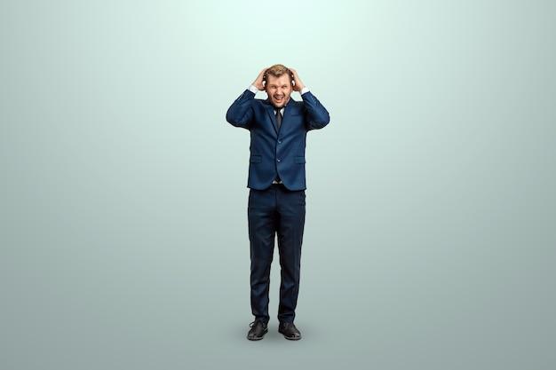 Mężczyzna w niebieskim garniturze zmęczony pracą, emocjonalną ciężką pracą warto krzyczeć z przeciążenia