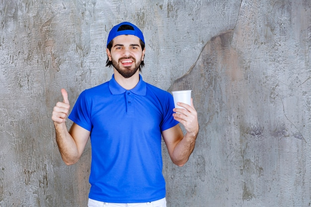 Mężczyzna w niebieskim mundurze trzymający napój na wynos i pokazujący znak pozytywnej dłoni.