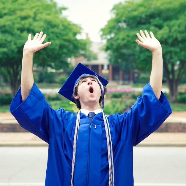 Mężczyzna w niebieskim płaszczu cieszący się wolnością po ukończeniu studiów