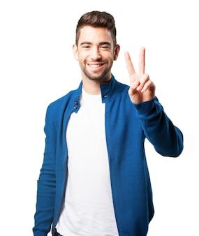 Mężczyzna w niebieskim płaszczu z palcami zwycięstwa