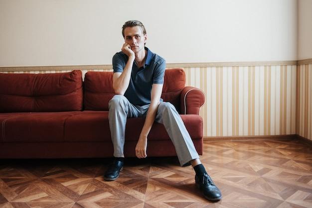 Mężczyzna w niebieskim polo pozuje do reklamy odzieży męskiej. strzelanie do sklepu z odzieżą męską