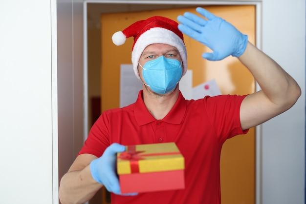 Mężczyzna w niebieskim respiratorze i rękawiczkach trzyma pudełko z prezentem i macha na powitanie.