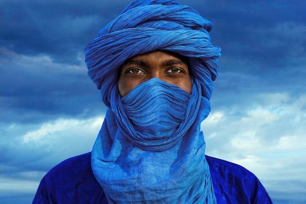 Mężczyzna w niebieskim turbanie pozuje w obozie w pobliżu timbuktu