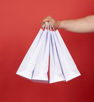 Mężczyzna w niebieskim ubraniu trzyma stos białych papierowych toreb