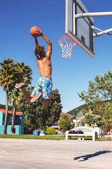 Mężczyzna w niebiesko-żółtych spodenkach robi wsad na boisku do koszykówki w ciągu dnia