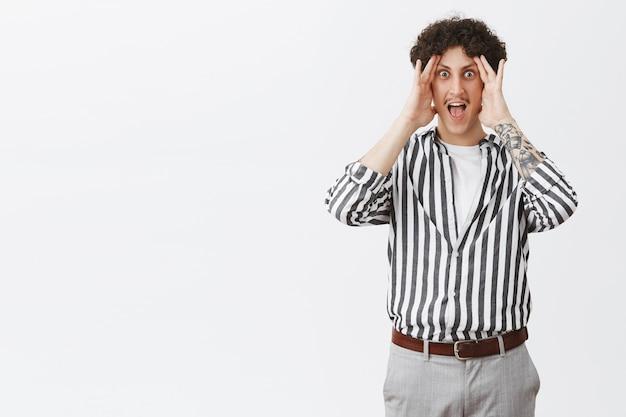 Mężczyzna w niezręcznej sytuacji krzyczy, próbując nie patrzeć na bok, trzymając dłonie nad twarzą, krzyczy i wytrzeszczają oczy, zdumiony i zdumiony, stojący w stylowej koszuli w paski i spodniach na szarej ścianie