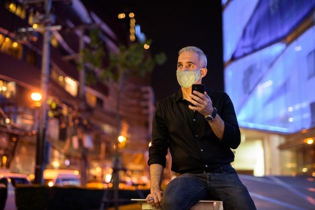 Mężczyzna w nocy na ulicach nosi ochronną maskę na twarz, aby chronić się przed wirusem koronawirusa 19 podczas korzystania z telefonu komórkowego i myślenia