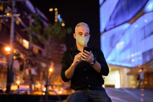 Mężczyzna w nocy na ulicach nosi ochronną maskę na twarz, aby chronić się przed wirusem koronawirusa 19 podczas korzystania z telefonu komórkowego