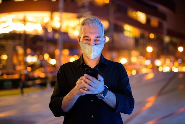 Mężczyzna w nocy na ulicach nosi ochronną maskę na twarz, aby chronić się przed wirusem koronawirusa 19 podczas korzystania z telefonu