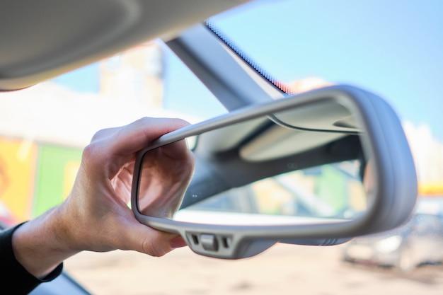 Mężczyzna w nowoczesnym samochodzie. ręka reguluje lusterko wsteczne.
