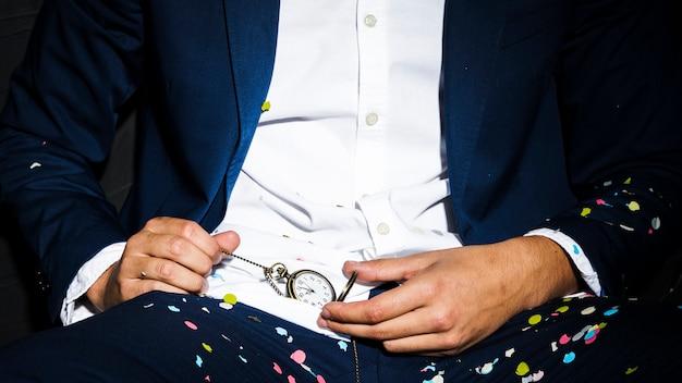 Mężczyzna w obiadowej kurtce trzyma kieszeniowego zegarek między confetti