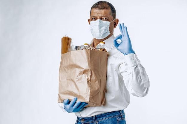 Mężczyzna w ochronnej masce medycznej z torbą ze sklepu spożywczego. dostawa jedzenia