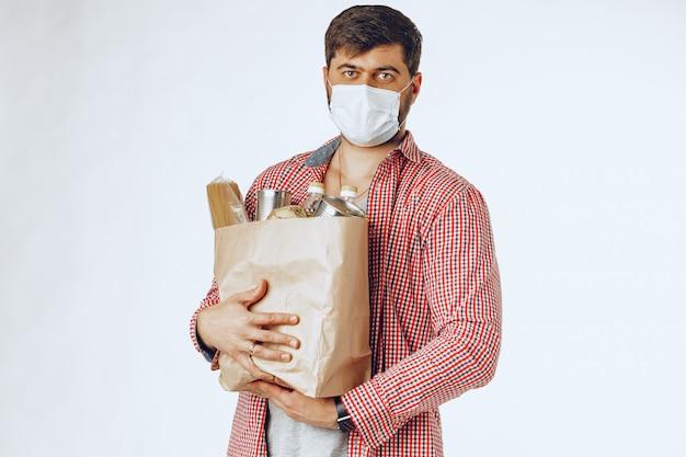Mężczyzna w ochronnej masce medycznej z torbą ze sklepu spożywczego