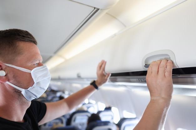 Mężczyzna w ochronnej masce medycznej zamykający bagażnik na bagaż w samolocie