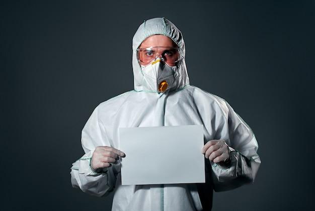 Mężczyzna w ochronnym białym kombinezonie, z maską i okularami na twarzy, z kartką papieru, puste miejsce na napis.