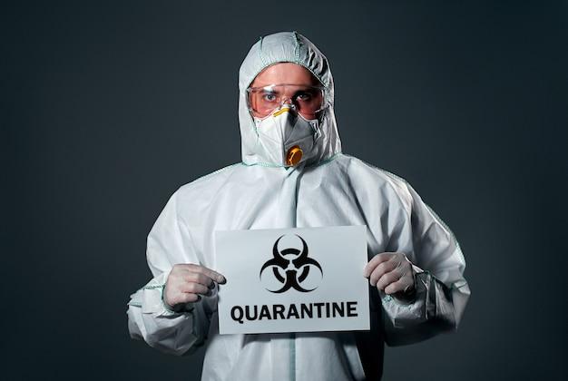 Mężczyzna w ochronnym białym kombinezonie, z maską i okularami na twarzy, z kartką papieru, z napisem quarantine.