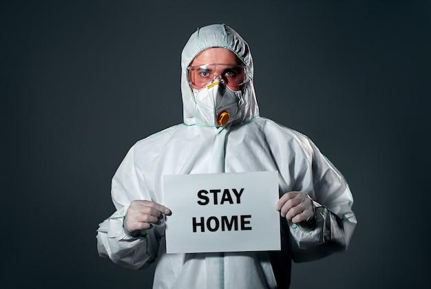 Mężczyzna w ochronnym białym kombinezonie, z maską i okularami na twarzy, z kartką papieru, z napisem stay home.