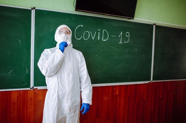 Mężczyzna w ochronnym kombinezonie antybakteryjnym stoi przy zielonej tablicy z napisem covid-19. pracownik odkażania wyjaśnia zagrożenie koronawirusem w szkole. opieka zdrowotna uczniów i studentów.