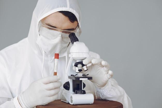 Mężczyzna w ochronnym kostiumu i szkłach pracuje przy laboratorium