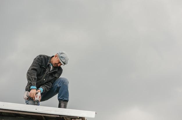 Mężczyzna w odzieży roboczej dokręca śrubami śrubokrętem dach na pochmurnym niebie