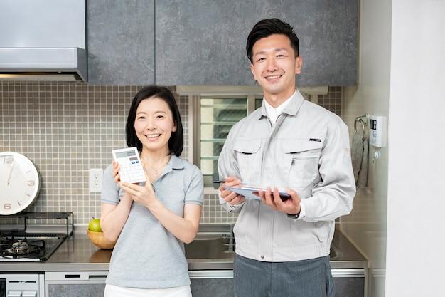 Mężczyzna w odzieży roboczej i kobieta z kalkulatorami w pokoju