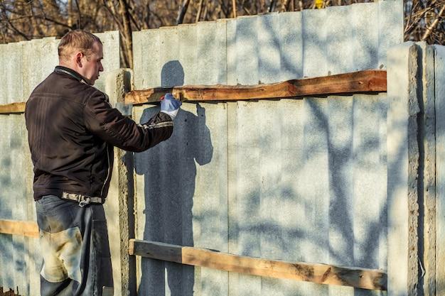 Mężczyzna w odzieży roboczej i rękawicach ochronnych maluje drewnianą deskę za pomocą ochronnego pędzla