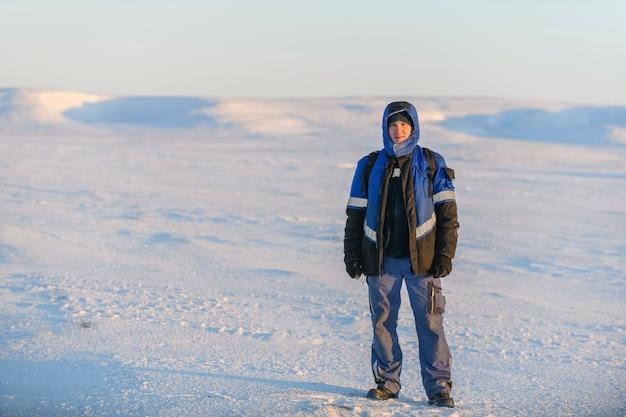 Mężczyzna w odzieży roboczej w zimowej tundrze.