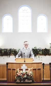 Mężczyzna w oficjalnym stroju głoszący biblię z trybuny przy ołtarzu kościoła