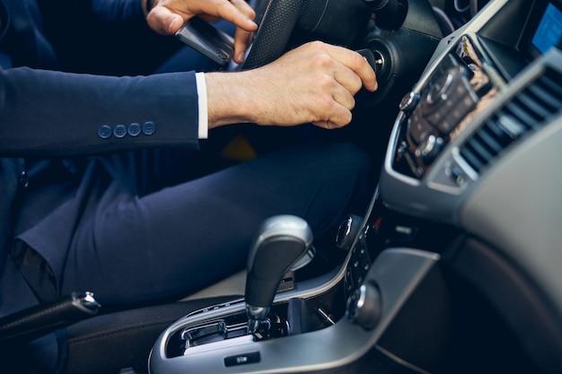 Mężczyzna w oficjalnym stroju uruchamia silnik samochodu za pomocą kluczyka