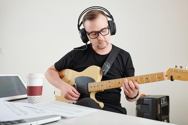 Mężczyzna w okularach, gra na gitarze